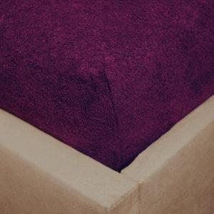 Prześcieradło frotte z gumką bakłażanowe na rogu łóżka firmy TuliSen.