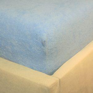 Prześcieradło frotte z gumką błękitne na rogu łóżka firmy TuliSen.