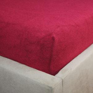 Prześcieradło frotte z gumką bordowe na rogu łóżka firmy TuliSen.