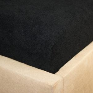 Prześcieradło frotte z gumką czarne na rogu łóżka firmy TuliSen.