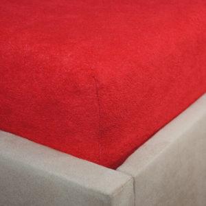 Prześcieradło frotte z gumką czerwone na rogu łóżka firmy TuliSen.