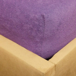 Prześcieradło frotte z gumką fioletowe na rogu łóżka firmy TuliSen.