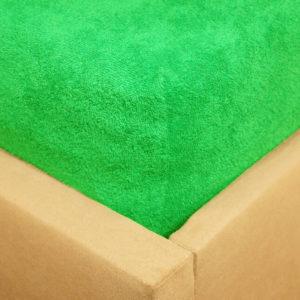Prześcieradło frotte z gumką w kolorze jaskrawej zieleni na rogu łóżka.