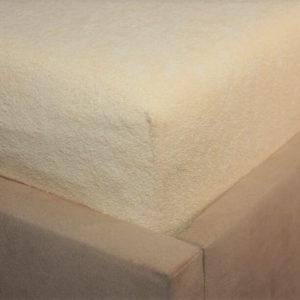 Prześcieradło frotte z gumką jasno morelowe na rogu łóżka firmy TuliSen.
