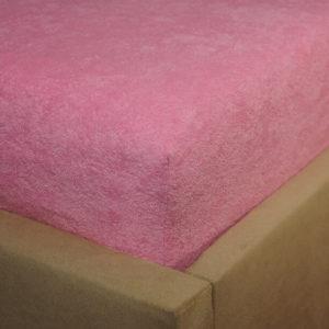 Prześcieradło frotte z gumką jasno różowe na rogu łóżka firmy TuliSen.