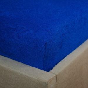 Prześcieradło frotte z gumką kobaltowe na rogu łóżka firmy TuliSen.