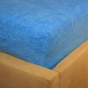 Prześcieradło frotte z gumką niebieskie na rogu łóżka firmy TuliSen.