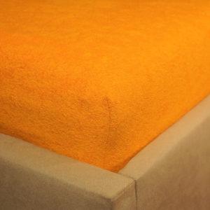 Prześcieradło frotte z gumką w zgaszonej pomarańczy na rogu łóżka firmy TuliSen.