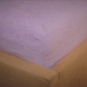 Prześcieradło frotte z gumką wrzosowe na rogu łóżka firmy TuliSen.
