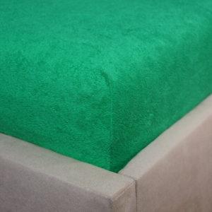 Prześcieradło frotte z gumką zieleń trawy na rogu łóżka firmy TuliSen.