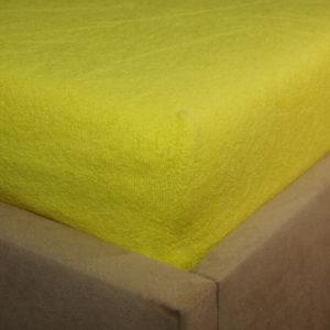 Prześcieradło frotte z gumką cytrynowe na rogu łóżka firmy TuliSen.