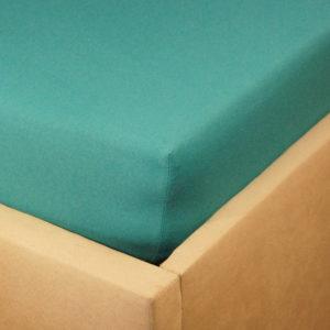 Prześcieradło jersey z gumką w kolorze butelkowej zieleni na rogu łóżka.