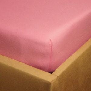 Prześcieradło jersey z gumką jasno różowe na rogu łóżka firmy TuliSen.