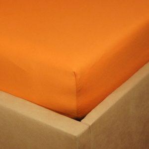 Prześcieradło jersey z gumką o kolorze zgaszonej pomarańczy na rogu łóżka.