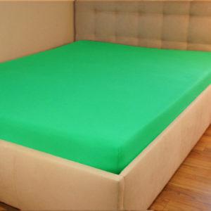 Prześcieradło jersey z gumką zieleń trawy na łóżku firmy TuliSen.