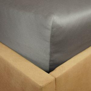 Prześcieradło satyna bawełniana z gumką szare na rogu łóżka firmy TuliSen.